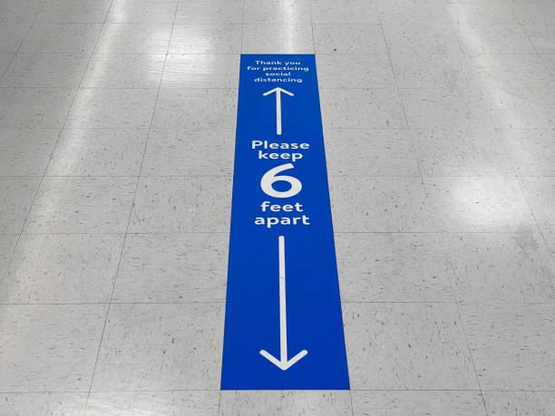 社會離散地板標誌警告6英尺的人之間的安全距離。公共衛生措施,以防止新的冠狀病毒covid-19感染的進一步傳播。 - 標誌 個照片及圖片檔