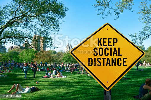 New York City, NY, USA - May 11, 2014: Social distance warning sign in front of New Yorkers enjoying a sunny weekend in Central Park, New York City, USA