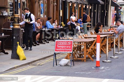 London, United Kingdom - July 12 2020: Social distancing cafe and restaurant temporary street seating in Old Compton Street, Soho