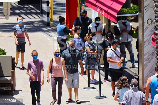 San Diego, CA May 25, 2020   line of shoppers wearing masks waiting to enter recently opened stores due to social distancing over the Memorial Day weekend