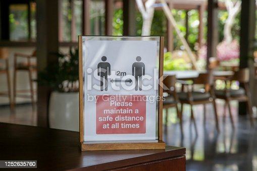 Social distancing sign at the entrance of restaurant as a reminder that everyone needs to comply with new requirements by maintaining a 2 meters distance to protect themselves and others from the Corona virus spread.