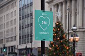 London, United Kingdom - November 27 2020: View of a social distancing sign with a Christmas tree in the background on Regent Street St James's, Waterloo Place.