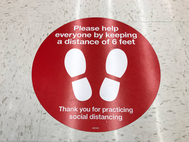 Social Distancing sign on the floor of supermarket Social Distancing sign on the floor of supermarket requesting customers to practice distance of at least 6 feet in order to prevent spread of coronavirus - San Jose, California, USA - March, 2020 flatten the curve stock pictures, royalty-free photos & images