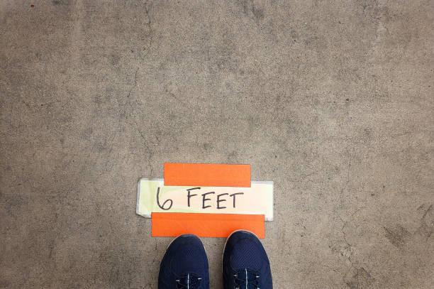 Soziale Entfernung - sechs Fuß Markierung Zeichen auf dem Bürgersteig in der Nähe von Ladeneingang – Foto