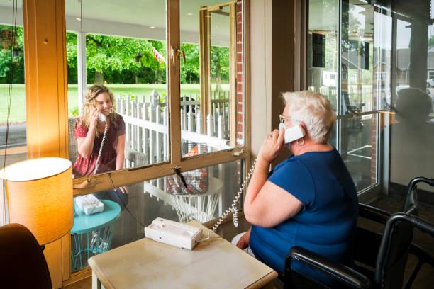sociaal distantiëren door een venster - raam bezoek stockfoto's en -beelden