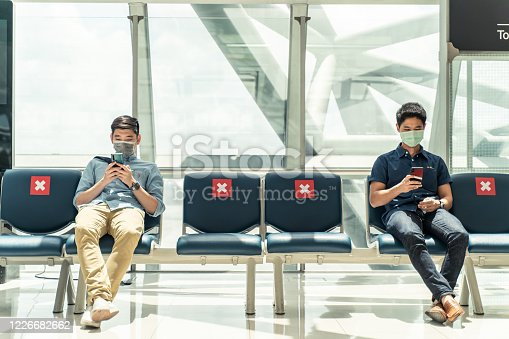istock Social distancing, two men wearing face mask sitting keeping distance away from each other to prevent covid19 infection during pandemic. Empty chair seat red cross shows avoidance in airport terminal. 1226682662