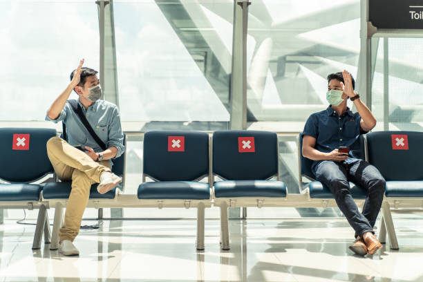social distancing, two men wearing face mask sitting keeping distance away from each other to prevent covid19 infection during pandemic. empty chair seat red cross shows avoidance in airport terminal. - new normal foto e immagini stock