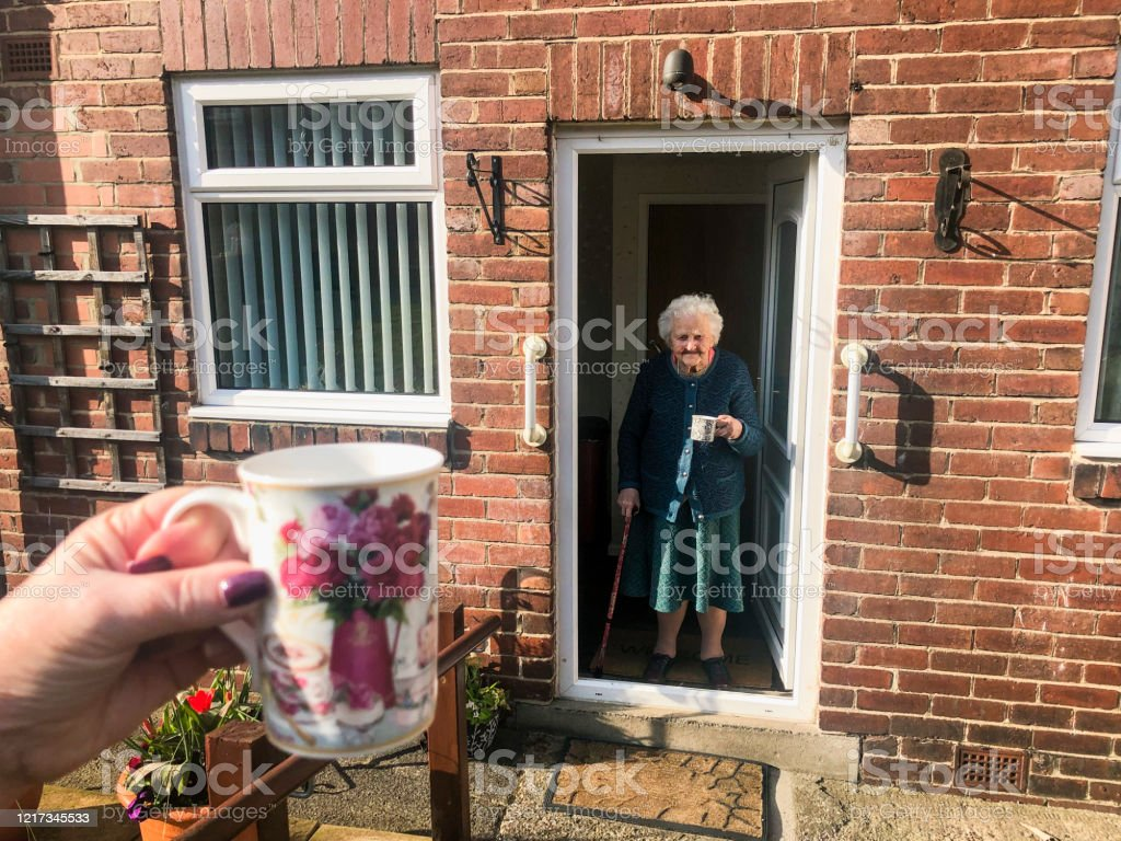 Social Distancing with Family Point of view angle of an unrecognisable person social distancing from her grandmother. She is sitting outside as her grandmother stands in the doorway of her house. 90 Plus Years Stock Photo