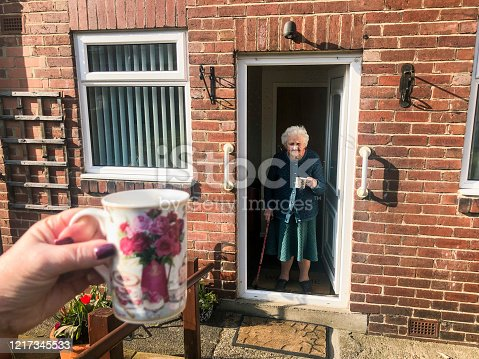 Point of view angle of an unrecognisable person social distancing from her grandmother. She is sitting outside as her grandmother stands in the doorway of her house.