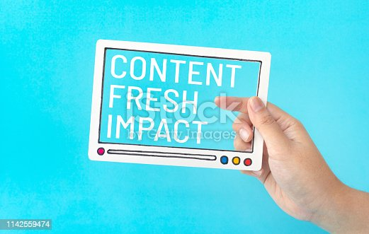 881845218 istock photo Social entertainment and online marketing concepts with female holding fram of video movie and marketing word on blue color 1142559474