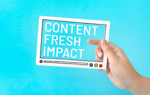 1125605742 istock photo Social entertainment and online marketing concepts with female holding fram of video movie and marketing word on blue color 1142559474