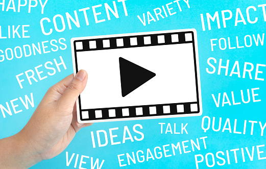 1125605742 istock photo Social entertainment and online marketing concepts with female holding fram of video movie and marketing word on blue color 1142652358