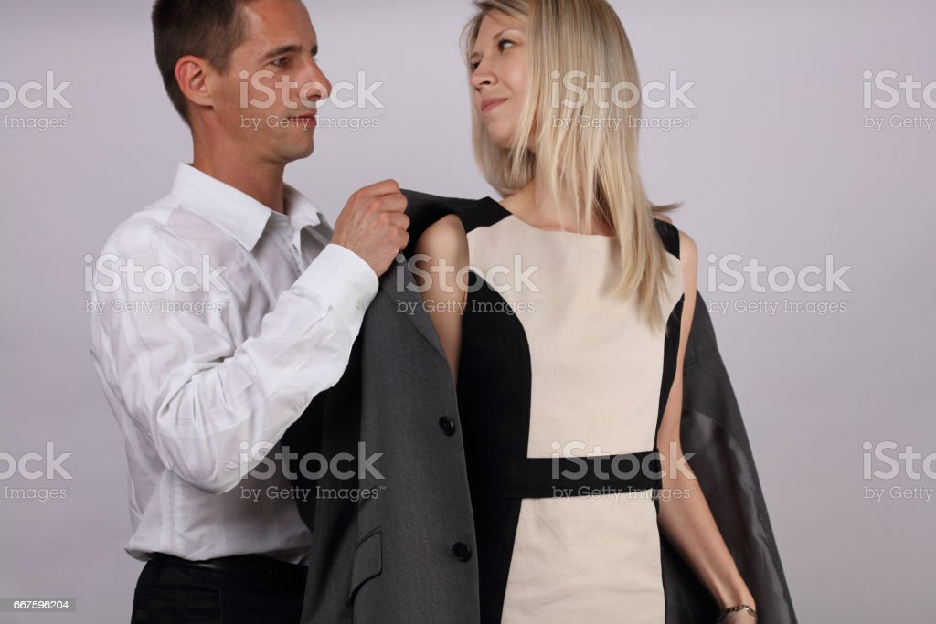 Social etiquette. Man giving a woman his jacket. Gentleman behavior....