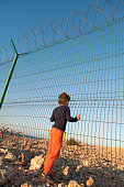 istock social issue concept of little refugee poor kid in orange pants holding high fence with barbed wire in desert in displaced persons camp 1222908959