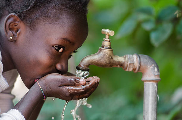 social issues: african black child drinking fresh water from tap - africa 個照片及圖片檔