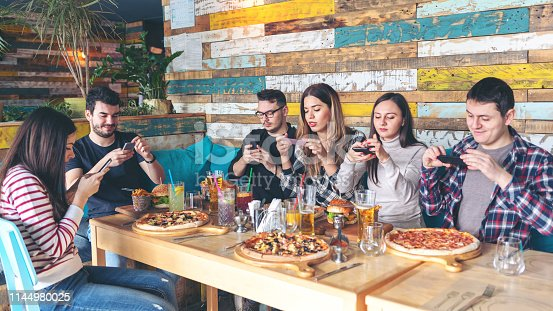 istock Social media addiction concept with young people photographing food in rustic restaurant, happy friends taking picture of pizza and hamburgers with mobile phones to post online, connecting millennials 1144980025