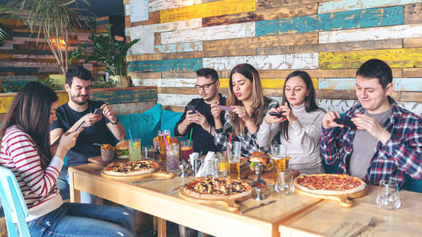 social media addiction concept with young people photographing food in rustic restaurant, happy friends taking picture of pizza and hamburgers with mobile phones to post online, connecting millennials - foodie stock photos and pictures