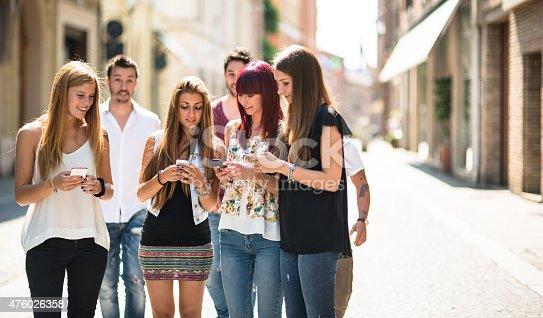 644191686 istock photo social media addiction people using the smartphone on the street 476026358