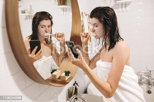 Social media affect. Young happy woman in white towel brushing teeth and looking at phone screen in stylish bathroom at round mirror. Slim sexy woman daily routine after shower.