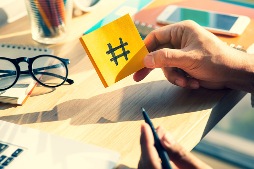 1125605742 istock photo Social media and creativity concepts with person writing hashtag sign  on notepaper 1207438892