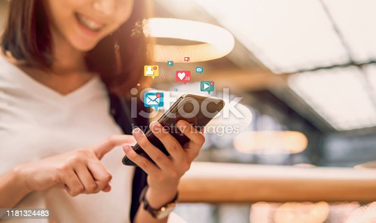 istock Social media and digital online concept, smiling Asian woman using smartphone and show technology icon. 1181324483