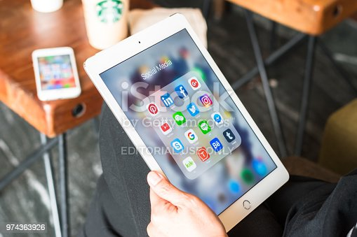 istock Social media app icons on Ipad, Iphone 7 smart phone touchscreen mobile internet technology lifestyle in digital 4.0 age. 974363926