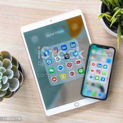istock Social media app, mobile multi-channel, cross-channel internet online application for people digital lifestyle with logo on iPhone X and ipad pro touchscreen 1159101776