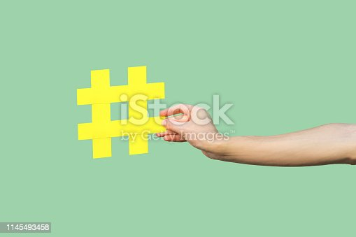Social media concept, closeup portrait of hand holding large big yellow hash tag sign. Indoor, isolated, copy space, green background, marketing symbol, instagram followers
