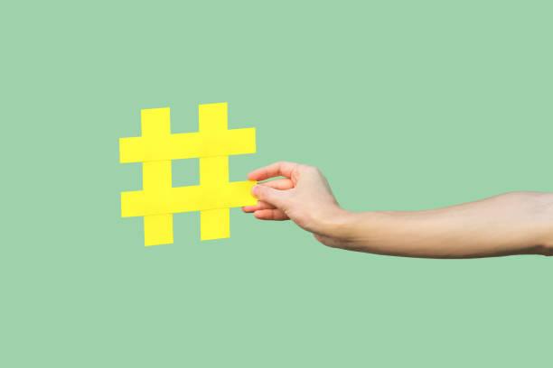 conceito social dos media, retrato do close up da mão que prende o grande sinal amarelo grande do tag da mistura. - lifestyle color background - fotografias e filmes do acervo