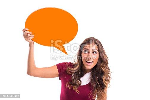 Young girl holding orange speech bubble, isolated on white background.