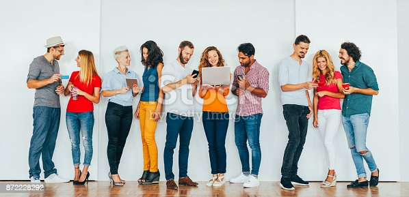 Large group of people using different portable devices.