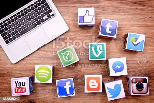 İstanbul, Turkey - January 16, 2016: Paper cubes with Popular social media services icons, including Facebook, Instagram, Youtube, Twitter and a Macbook Pro laptop computer on a wooden desk.