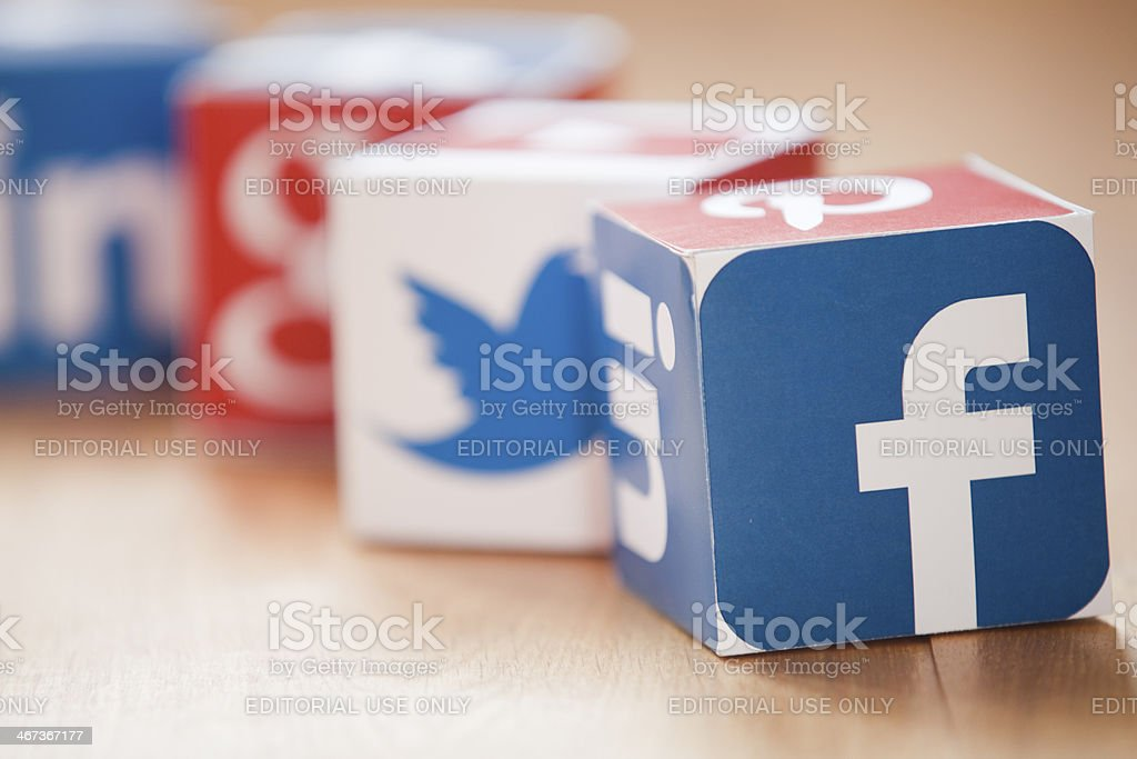Social media cubes on a wooden background London, United KIngdom- February 3, 2014: Social media logos printed onto handmade cubes. Logos include Facebook, linkedin, twitter. Social media uses web and mobile technology to connect people Arrangement Stock Photo