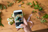 Directly above view of florist photographing prepared bouquet and sending photo message to customer