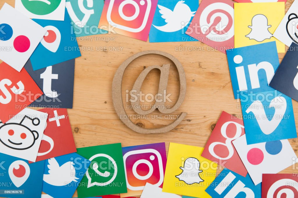 Social media icons and at symbol on a wooden background stock photo