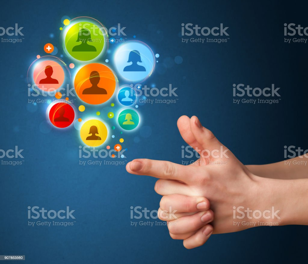 Social media icons coming out of gun shaped hand stock photo