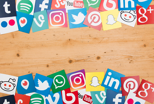 london, United Kingdom - September 5, 2016: A large collection of the most opular social media logos printed onto paper on a wooden background