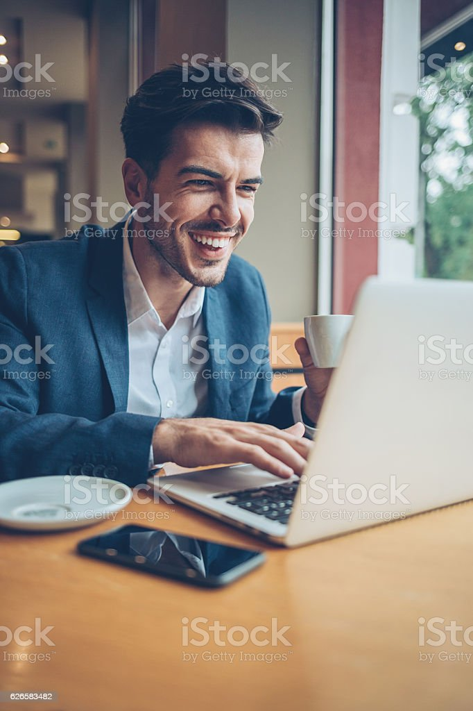 Smiling man in smart casual wear working on a laptop and drinking...