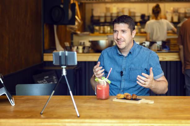 social media influencer or food blogger creating content inside small restaurant - man sharing online food review using smartphone on tripod and lavalier - smiling content creator vlogger filming video - dodatkowa praca zdjęcia i obrazy z banku zdjęć