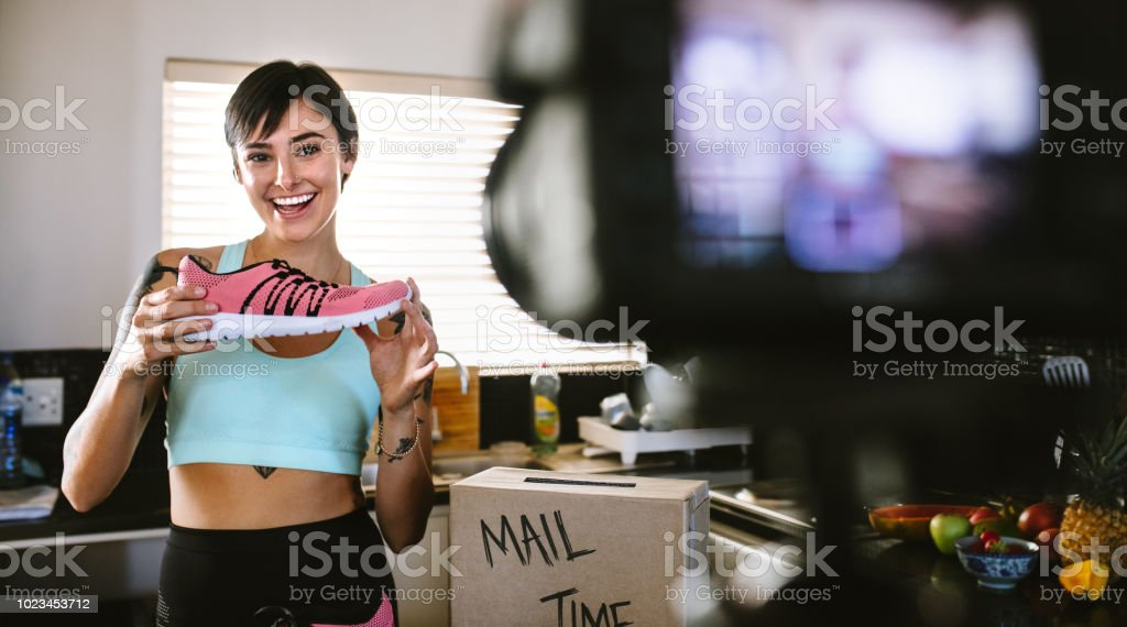 Social media influencer reviewing sports shoe stock photo
