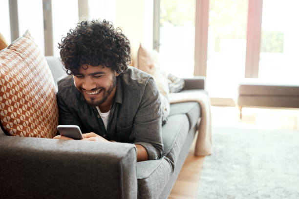 Social media is ablaze today! Shot of a handsome young man using his cellphone while relaxing on the couch at home ablaze stock pictures, royalty-free photos & images