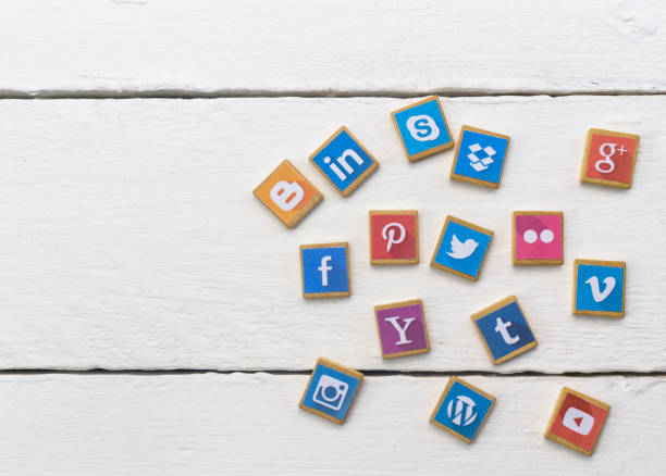 social media logotype popular collection printed and place on wood scrabble game pieces isolated on white wood planks - instagram стоковые фото и изображения