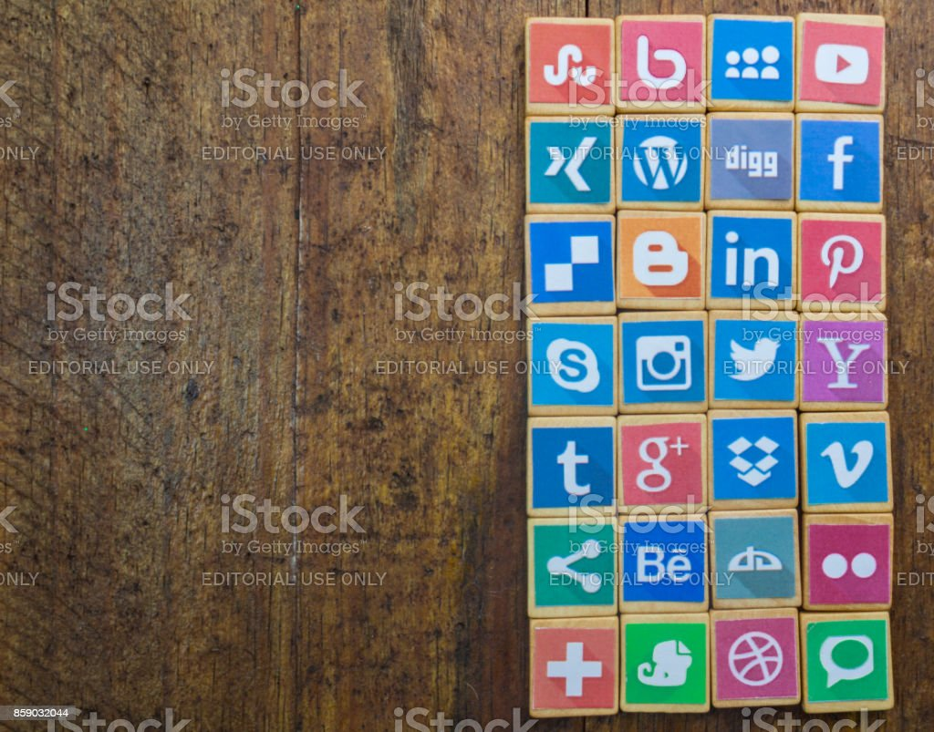 QUEENSTOWN, SOUTH AFRICA - 09 APRIL 2017: Social Media logotype popular collection printed and place on wood scrabble game pieces isolated on rustic brown wooden floor planks stock photo