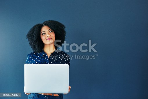 Studio shot of an attractive young woman looking thoughtful while using a laptop against a blue background