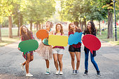 Group of girls holding color speech bubbles