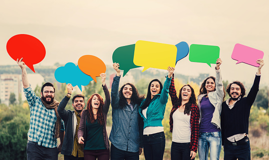 Group of people holding colorful speech bubbles on a roof.
