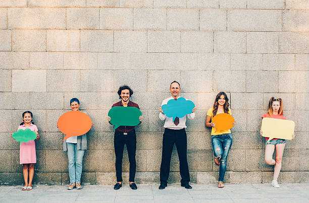 Social Media Group of people at different ages holding colorful speech bubbles. age contrast stock pictures, royalty-free photos & images