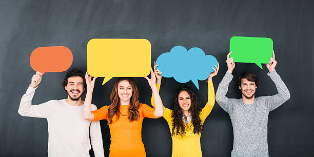 Social Media Group of people holding colorful speech bubbles in front of a blackboard. speech bubble stock pictures, royalty-free photos & images