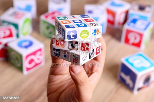 İstanbul, Turkey - January 17, 2017: Hands holding a Rubik's Cube covered by social media icons on a wooden desk. Paper cubes also with Popular social media services icons, including Facebook, Instagram, Youtube, Twitter.