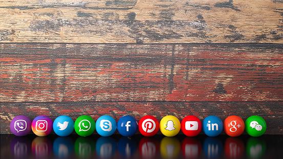 Istanbul, Turkey - November 04, 2018: Sphere shape of popular social media services icons, including Facebook, Instagram, Youtube, Twitter, Whatsapp, Linkedin, Snapchat, Pinterest, Viber, Google, Wechat, Skype on a wooden desk